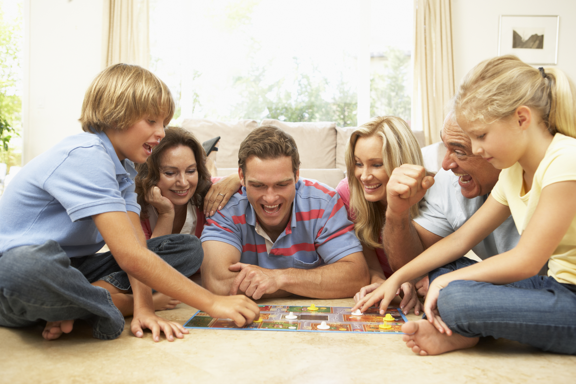 Family Playing Board Game At Home With Grandparents Watching